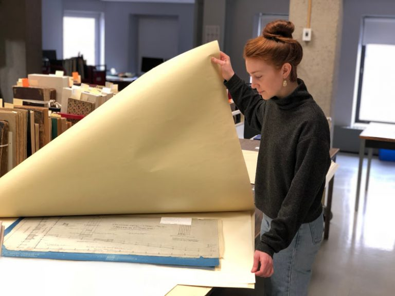 Heather Rogers looking at architectural plans in the digitization lab as a part of her practicum.