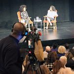 Esi Edugyan and Amanda Parris on stage with the audience and cameraman in the foreground.