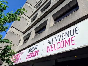 Banner above McLennan Library Building reads: Biblio/Library, Bienvenue, Welcome