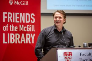 Stratford actor and director Jonathan Goad smiling at a podium in front of a red Friends of the Library banner at the 2019 Shakespeare Lecture on November 19, 2019