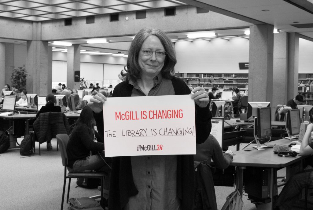 "Black and white photograph of Dean Colleen Cook in the McLennan Reading Room holding up a colour sign that says ""McGill is changing, the Library is changing"""