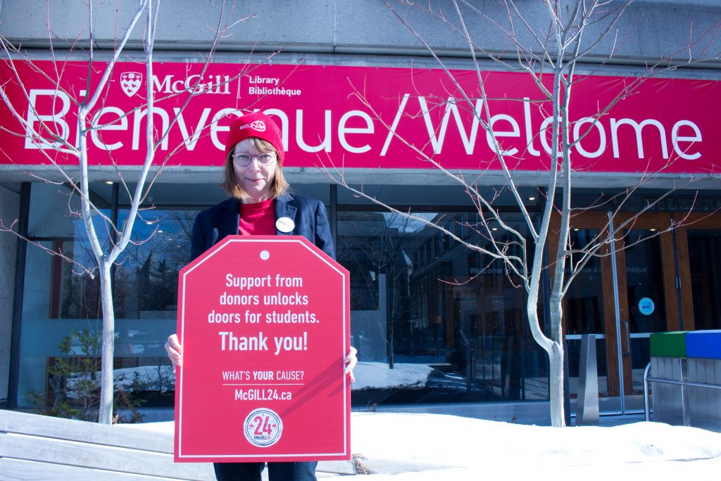"Dean Colleen Cook wearing a red McGill24 toque and t-shirt standing in front of the red Bienvenue/ Welcome banner holding a red poster that says ""Support from donors open doors for students"""""