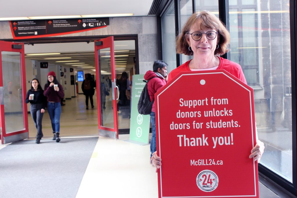 "Dean Colleen Cook on Redpath Bridge holding up a poster that says ""Support from donors unlocks doors for students"""