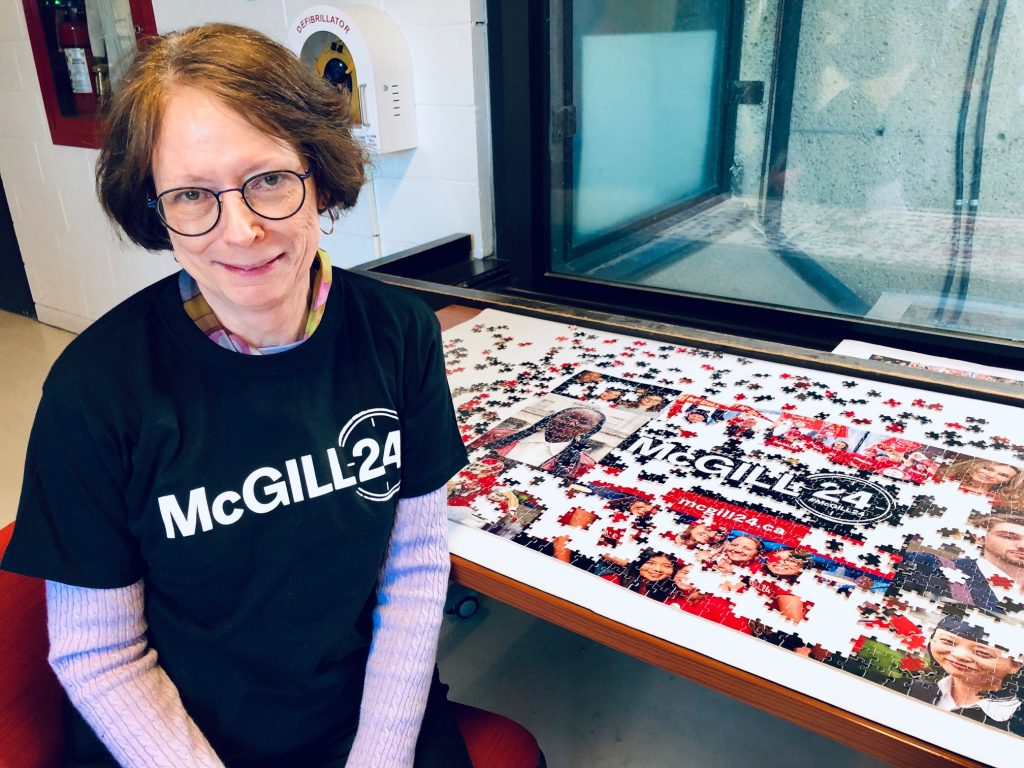 Dean Colleen Cook wearing a black McGill24 t-shirt sitting in front of a partially completed McGill24 puzzle featuring a collage of different photographs.