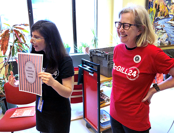 Two Library staff members wearing McGill24 t-shirts. One of them holding a photocopy of a cookbook cover.