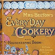 "Close up of gold cover of ""Mrs. Beeton's Everyday Cookery and Housekeeping Book"""