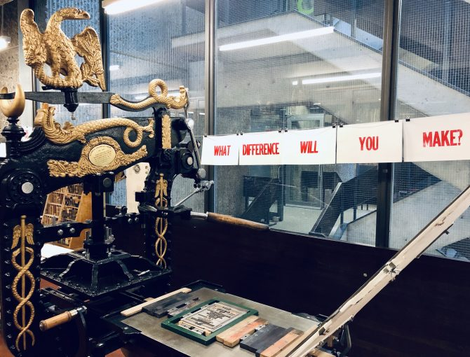 """Ornate black and gold Columbian printing press in foreground with prints """"what difference will you make?"""" hanging behind it."""