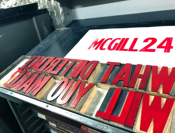 """Wood block letters inked in red and a sheet of paper with the words """"McGill24"""" centred in red ink."""