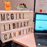 "Laptop and light box on desk with the words ""McGill Library can help!"""""