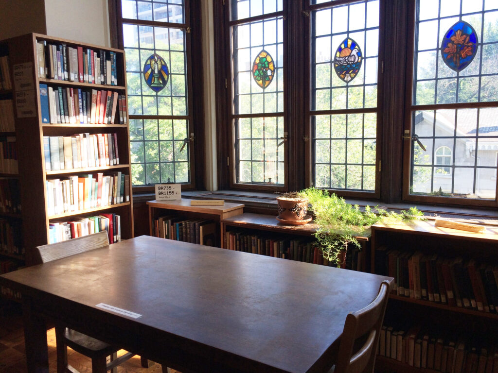 Corner of Birks Reading Room showing a wooden table, chairs, stained glass windows, and bookshelves.