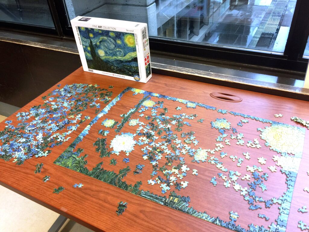 Partially completed puzzle on a wood table.