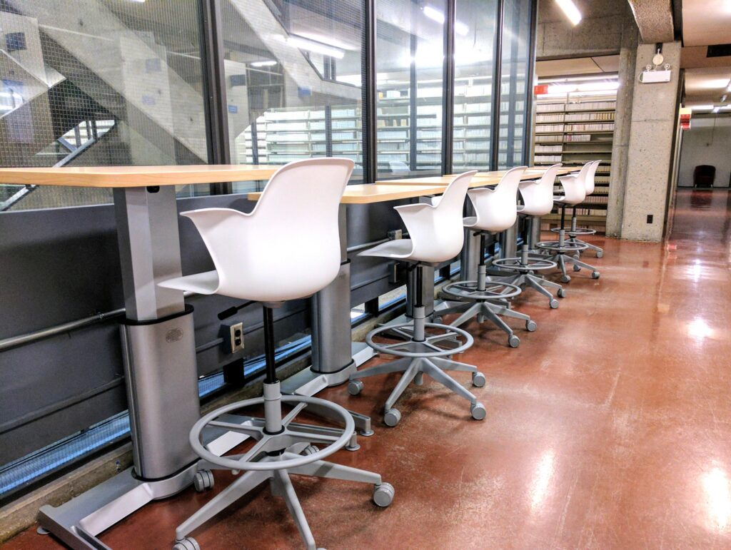 Row of high standing desks with white chairs.
