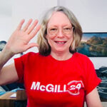 Dean Colleen Cook over Zoom in a red McGill24 t-shirt smiling and waving.