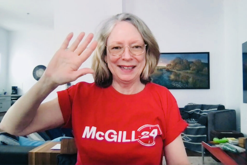 Dean Colleen Cook over Zoom smiling and waving in a Red McGill24 t-shirt.