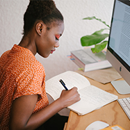 Woman sitting at a desk writing in a notebook with a file open on a desktop.
