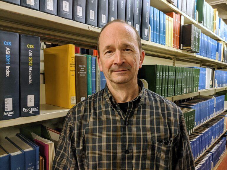 Steve Blaise in front of bookshelves.