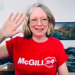 Colleen Cook in a red t-shirt at her desk waving to the camera
