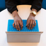 Hands seen from above on a blue Surface keyboard on a round table.